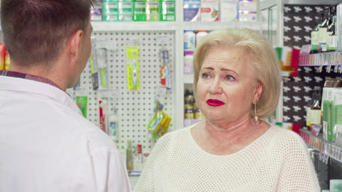 Senior woman with sore throat asking pharmacist for medicine Footage