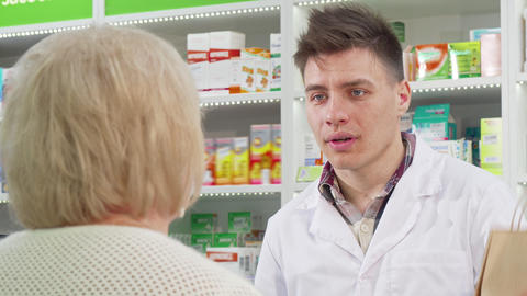 Handsome young pharmacist handing shopping bag with purchase to a customer Live Action