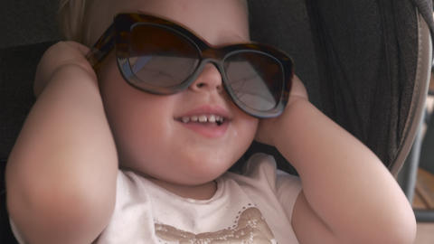 Lovely baby girl in mums sunglasses Live Action