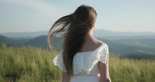 Attractive woman on a mountain peak with her long hair blowing in the wind Footage