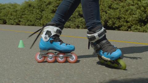 Female legs riding crisscross round cones outdoors Footage