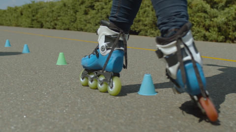 Woman roller's feet riding round cones in park GIF