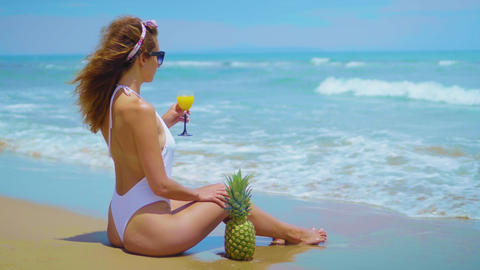 Cheerful beautiful young girl are sitting on the beach by the sea with pineapple Footage