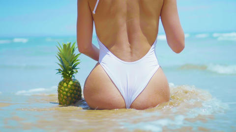 Closeup beautiful sexy young woman siting on the beach with pineapple. Sexy Live Action