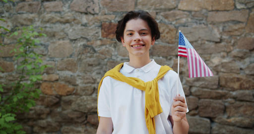 Portrait of attractive American teenage boy outdoors with US flag smiling Footage