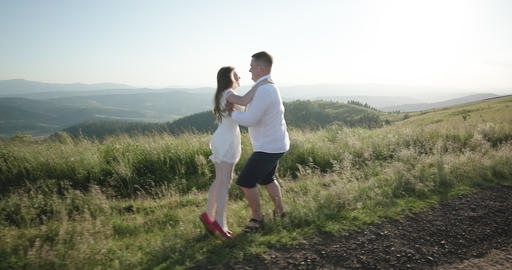 Couple walks along on a background of mountains. Two people walk along the Footage