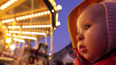 Baby looks at beautiful illuminated carousel in the evening Footage