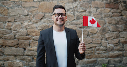 Portrait of handsome bearded guy waving Canadian flag standing outdoors alone Footage