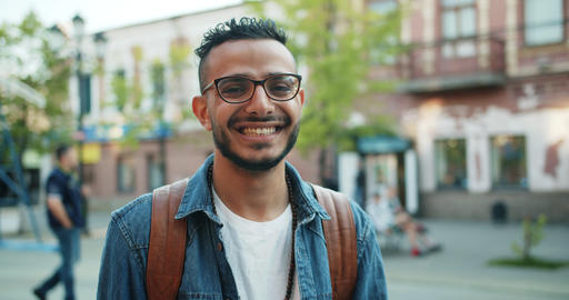 Portrait of good-looking student Middle-Eastern guy smiling in the street ビデオ