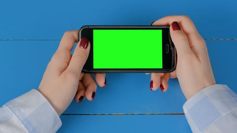 Woman looking at black smartphone with empty green screen - chroma key concept Live Action