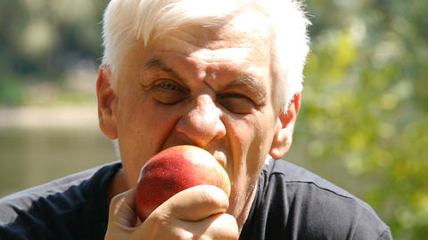Portrait of elderly man eating an apple. Close up. Man to eat an apple Footage