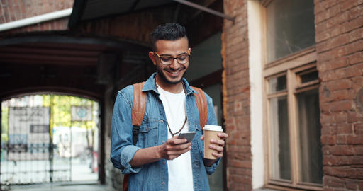 Cheerful young Arab touching smartphone screen holding coffee cup outdoors Footage