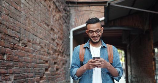 Handsome bearded Arab enjoying modern smartphone application smiling outdoors Footage
