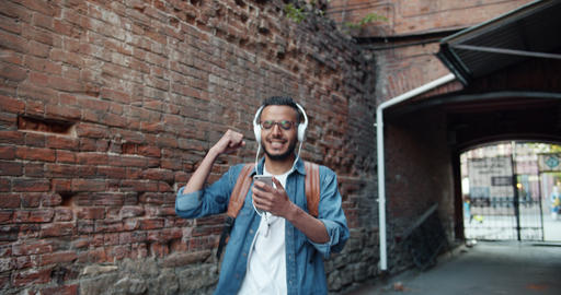 African American guy in headphones dancing singing outdoors holding smartphone Footage