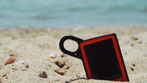 Portable solar charger power bank on the beach Live Action