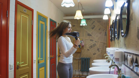 Hair care young woman blowing hair dryer on wet hair in public bathroom in front Live Action