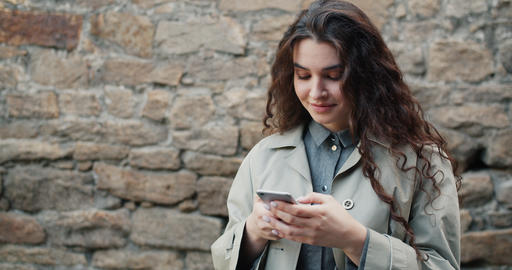 Slow motion of pretty girl using smartphone in street touching screen smiling Footage