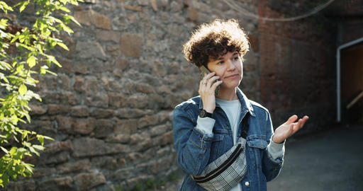 Portrait of joyful girl talking on mobile phone outdoors in the street smiling Footage