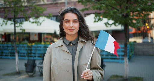 Slow motion portrait of cute French girl standing outdoors with flag of France Footage