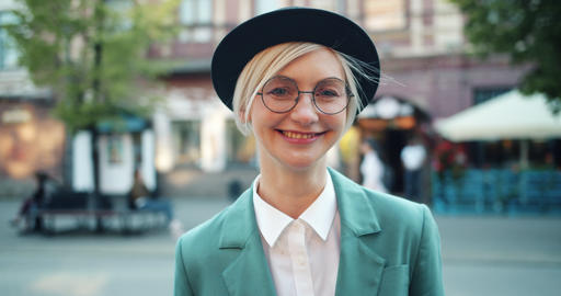 Portrait of joyful hipster in glasses and hat smiling standing outdoors alone Footage