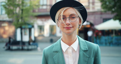 Portrait of attractive student blonde in hat and glasses smiling outdoors Footage