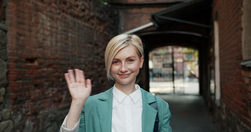 Slow motion portrait of pretty woman waving hand meaning hello outdoors Footage