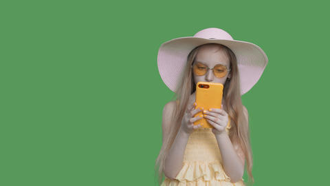 Child girl in summer hat reads phone on green wall background, alpha channel Footage