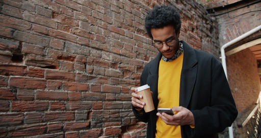 Slow motion of African American guy using smartphone holding coffee outdoors Footage