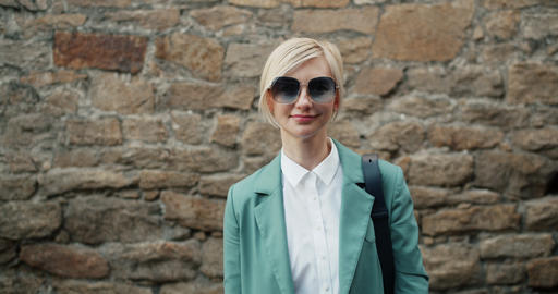 Portrait of pretty young lady in stylish sunglasses and modern clothing outdoors Footage