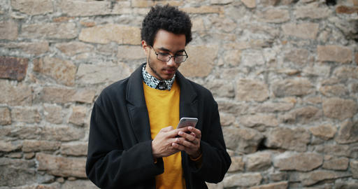 Slow motion of attractive African American man using smartphone outdoors Footage