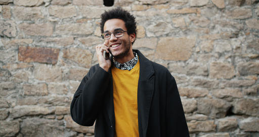 Slow motion of cheerful African American man talking on mobile phone outdoors Footage