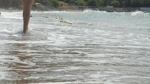 Active sporty barefoot woman walks along seashore in SLOW MOTION. Woman fitness Footage