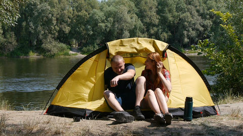 Concept of tourism and travel. Young happy couple sitting in tent watching the Live Action