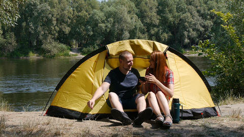 Content happy couple sitting in tent. Concept of tourism and travel. The girl Footage