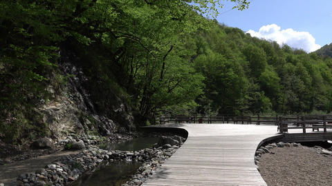 Gangway to observation desk on river bank, green mountains valley bottom Footage