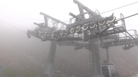 Gondola lift pass by intermediate pylon, close up wheels and haul steel cable Footage