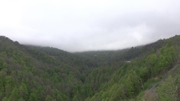 Low clouds over green valley, aerial mountainous area panorama, green trees Footage