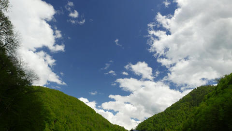 Cumulus clouds quickly run over green mountains Footage