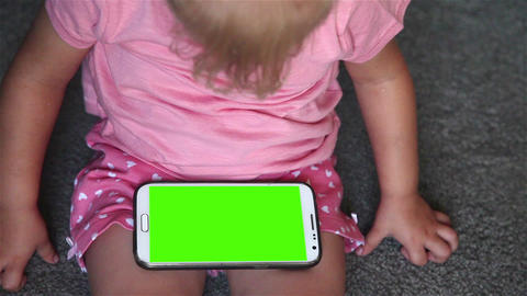 Close-up of a little girl uses a smart phone with green screen Footage