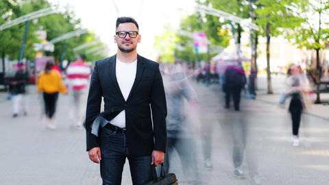 Zoom-out time lapse of handsome guy with bag standing outdoors in the street Footage