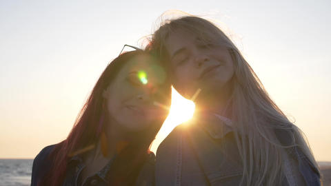 portrait of two young women leaning head to head against the sea with sunbeams Footage