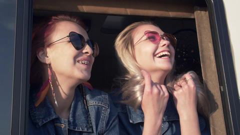 pair of young women in sunglasses with flowing hair in the sunset light Live Action