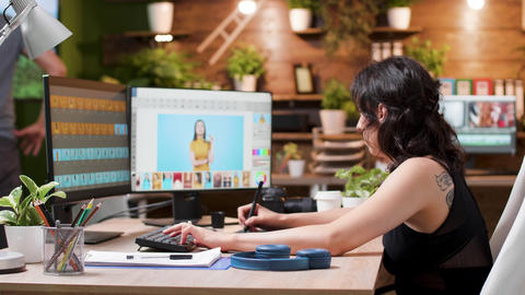 Female photographer edits photos in creative media agency office Live Action
