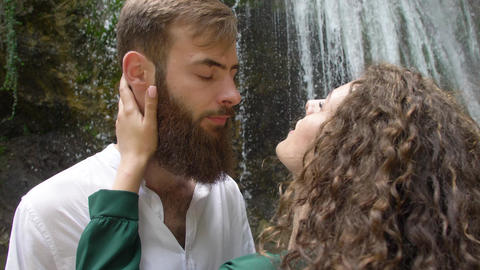 young beautiful woman embraces a young man with a beard and shakes hair against Live Action