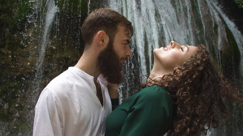 sexy young woman with curly blond hair in the arms of a young man with a beard Live Action