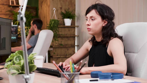 Woman designer sips coffee while working on the computer Footage