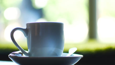 A cup of coffee in a cafe, a hand takes a cup and after a while puts it in its Live Action