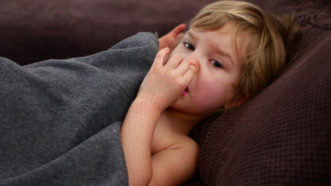 The girl pokes her finger in her nose. Pensive child Live Action