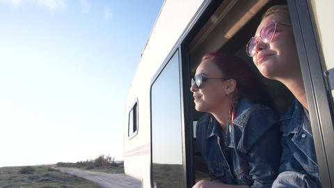 a pair of young women dressed in jeans looks out the window of an autotrailer Live Action