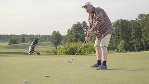 Cute old man playing golf alone on the golf field. Senior man hit the ball using Footage